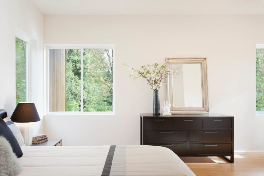 Bedroom features dark wood dressers and light bed coverings, matching the color palette throughout the home. Large windows on this top floor afford expansive views.