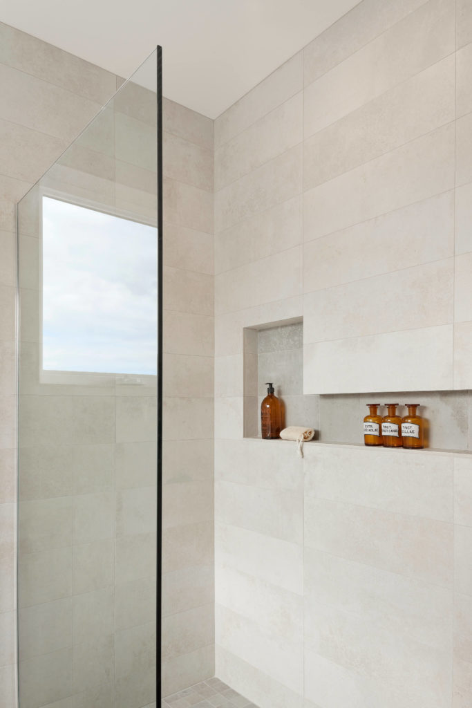 The open-design, glass enclosed shower features shelving set into the wall.