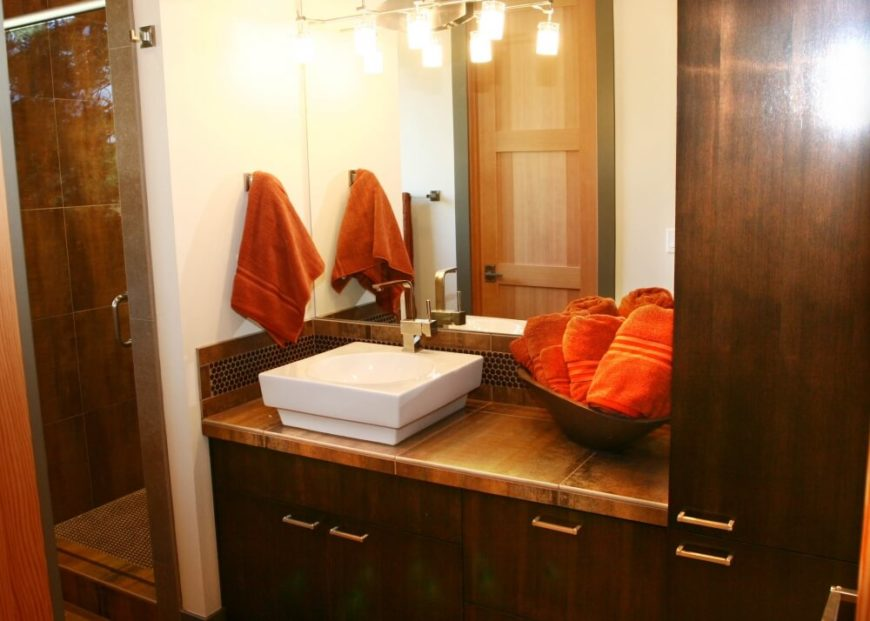 The master bedroom's suite continues the dark wood and bold orange-red of the bedding, but adds bronzed tile to the mix. A white square vessel sink pops against the countertops.