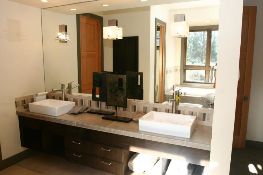 A spacious master bedroom with his-and-hers vessel sinks and towel storage beneath the right sink.