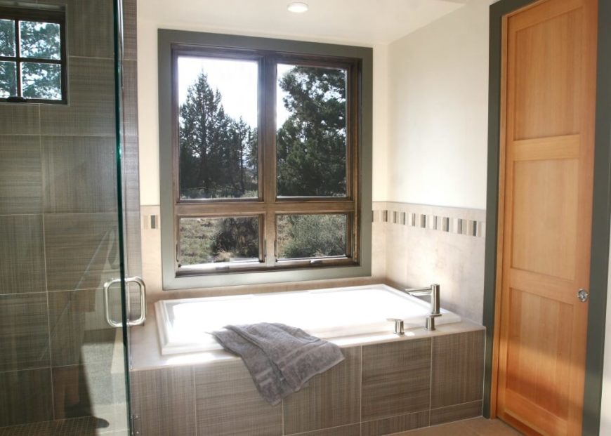 Across from the vanity is the large soaking tub in a tile enclosure and the glass-enclosed shower stall.