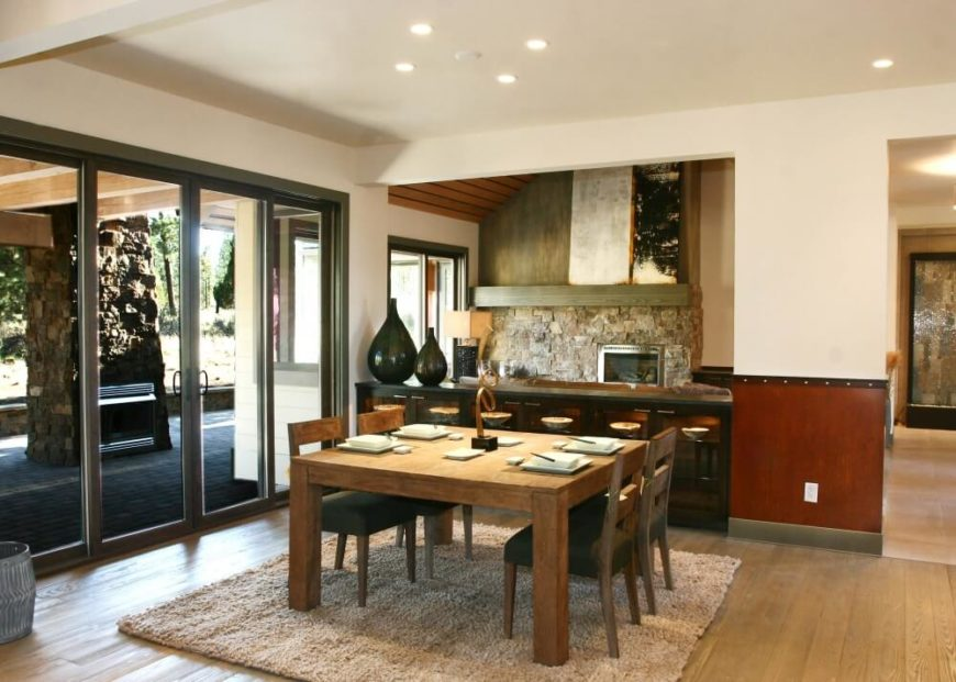 The adjacent dining room has a rustic natural wood table with seating for four. A buffet is set against the stone wall. Large double glass doors lead out onto the backyard patio.