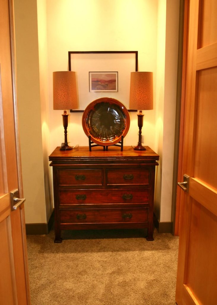 The entrance to the walk-in closet from the master bedroom has a small nook that contains a beautiful antique dresser.