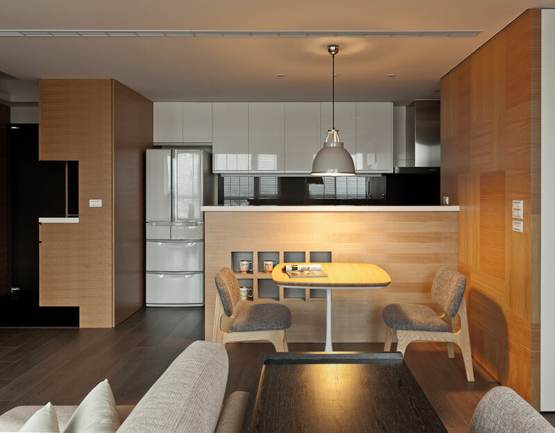 The kitchen features glossy white cabinetry and a matching refrigerator, separating its colors from the rest of the home.