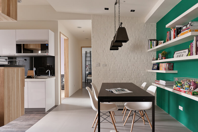 The dining area features a major splash of color in the form of this green wall at right, backing a set of minimalist white shelves.