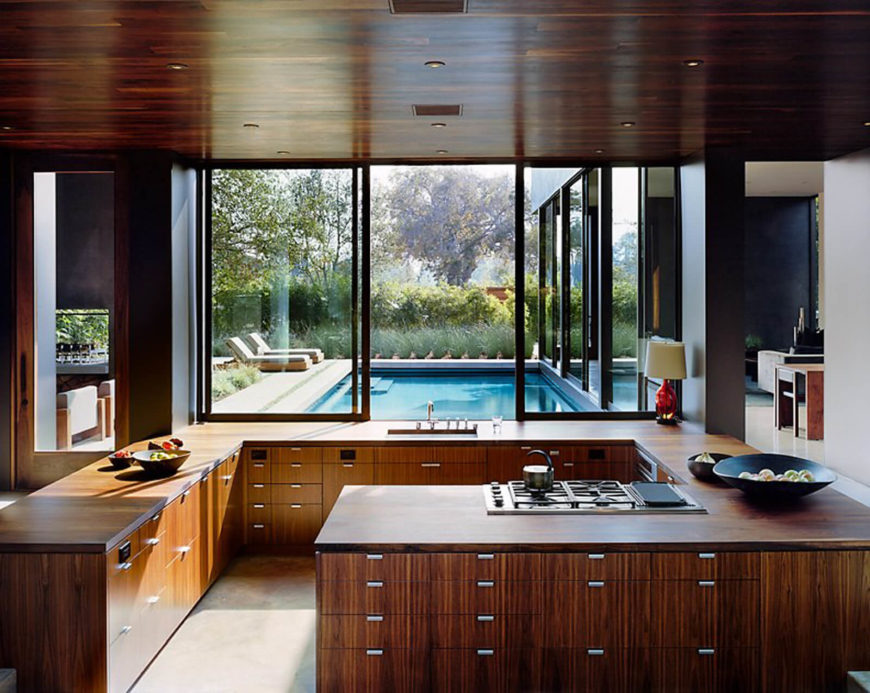 Here in the kitchen, a large wraparound wood countertop over sleek matching cabinetry carves out a cooking space, with full height windows sliding open to connect with the outdoors.
