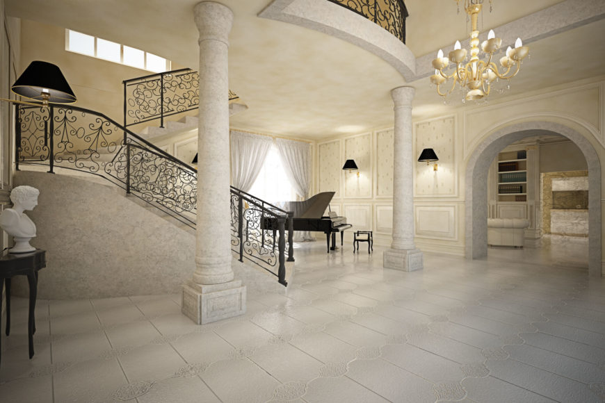 Entering the home, the grand spiral staircase commands attention over the open foyer space. Stone pillars, carved wood and gold leaf, and a singular black grand piano help make the elegant statement.