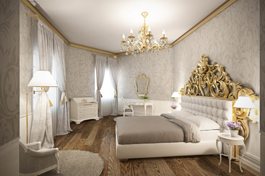 The bedroom wraps subtly patterned wallpaper around a space defined by gold details and white furniture. Natural hardwood flooring spreads beneath bed, traditionally styled seating, dresser, and small vanity.