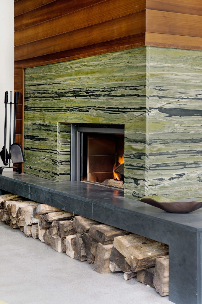 The fireplace stands over a dark slate tile structure housing firewood. The meeting of these textures with rich wood paneling creates a modern rustic palette.