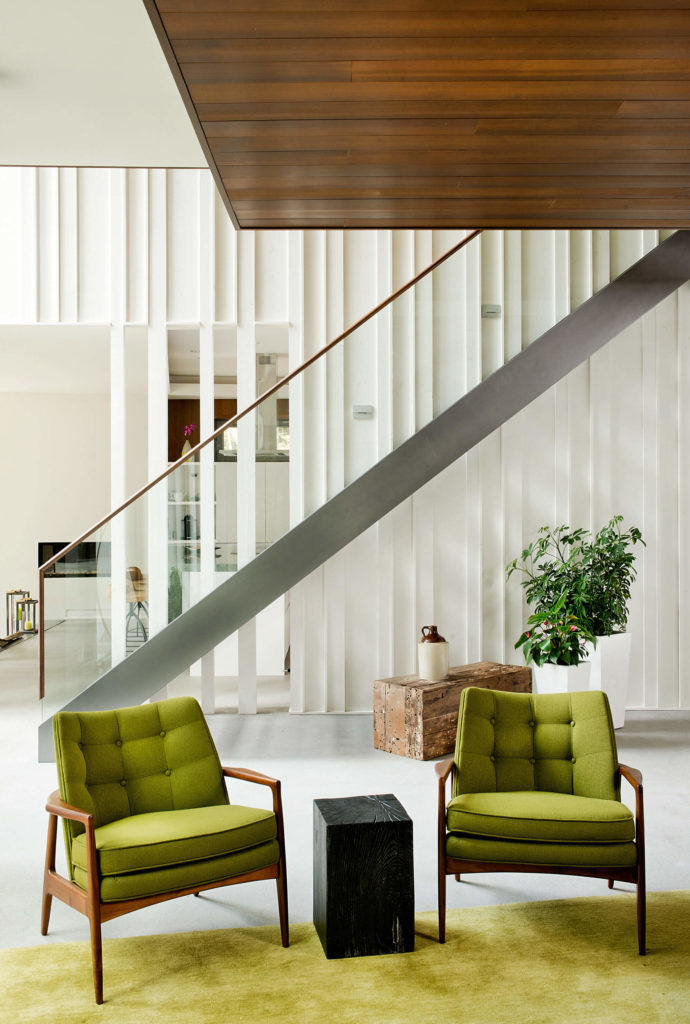 The bright green hues in the living room contrast perfectly with white surroundings. Here we see the profile view of the staircase, framed in metal and glass.