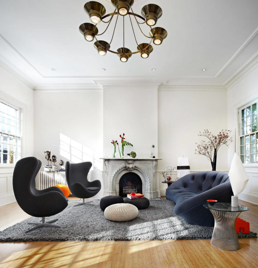 Here we see the full scope of the living room, with a set of curved modern seating options on a thick grey area rug over hardwood flooring. Bursts of color augment the classically shaped room, with an ornate marble fireplace at center.