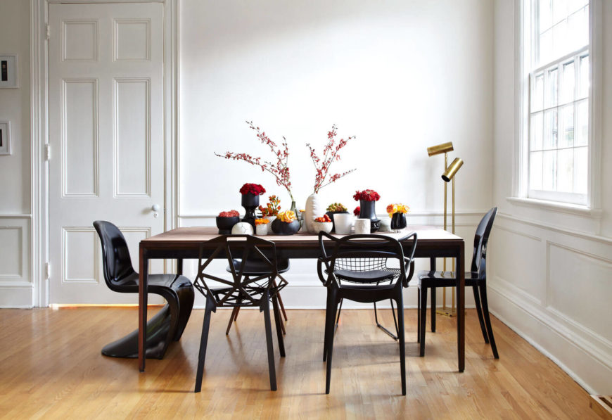 The dining room holds a slightly more traditional style, with this minimalist wood table surrounded by black chairs. Each chair is a completely different design from the next, making for interesting variety tied together by color.