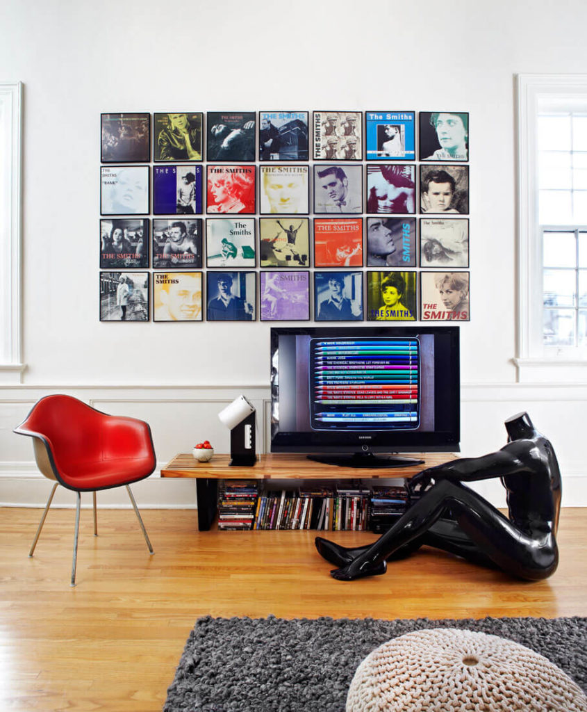 The multi-colored album art prints on this wall, floating above a custom entertainment table and red leather armchair, exemplify the playful yet restrained style of this home. One of several human forms graces the hardwood flooring here.