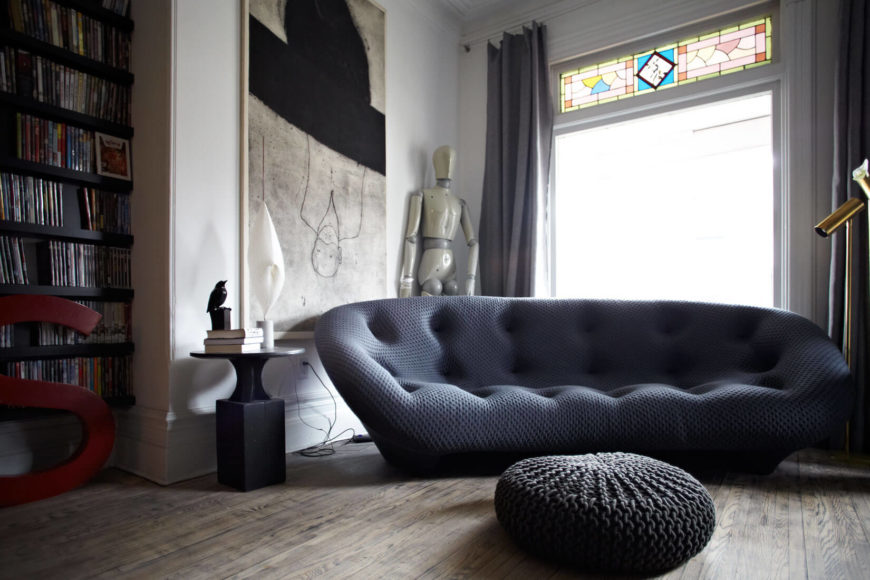 This sofa exemplifies the curved, contemporary furniture throughout the home, contrasting with stately white walls and muted hardwood flooring. Large art pieces appear throughout.