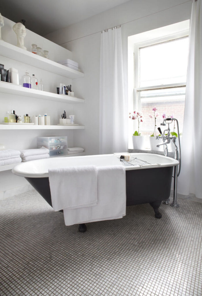 The master bath houses this traditional claw-foot tub over micro-tile flooring. White shelving and drapes brighten the space.