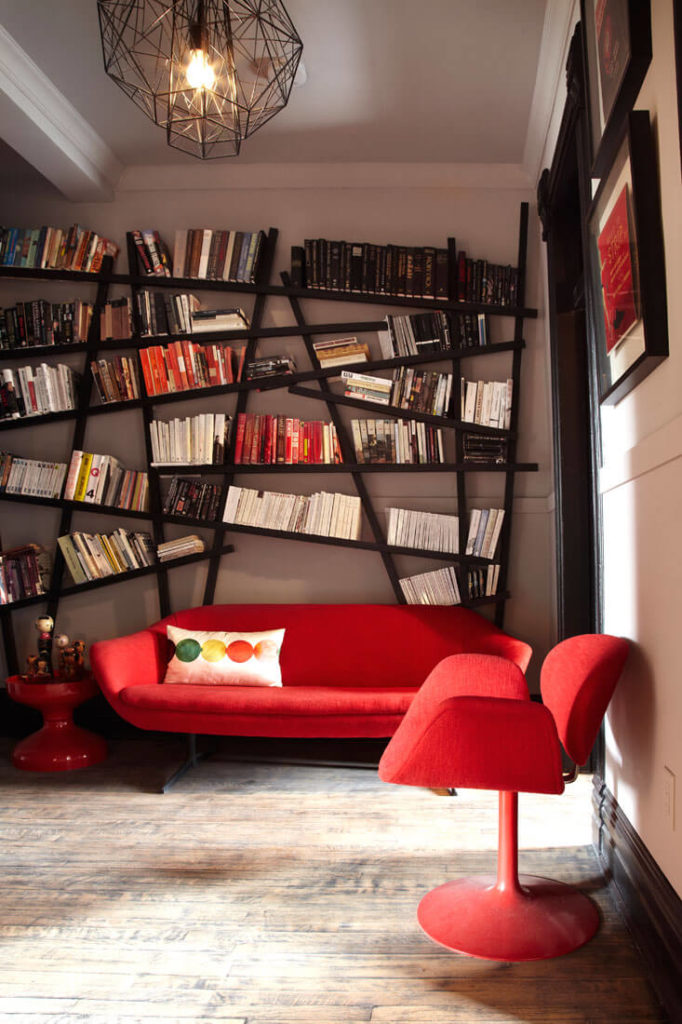 "This room features a unique ""haphazard"" modernist bookshelf, with angular black lines echoed in the lighting framework. Bright red furniture contrasts with sedate surroundings."
