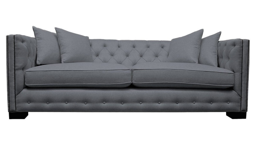 This elegant, rectangular grey sofa in fabric upholstery features an angular, low-slung frame with button tufting all around. A pair of overstuffed seat cushions complete the comfort.