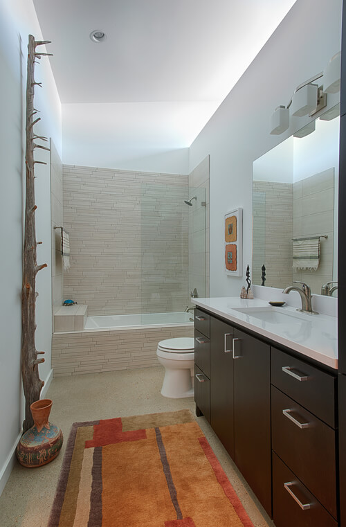 The bathroom reflects the elegant, detail-rich approach of the home, with dark cabinetry and sleek white countertop on the vanity, a glass shower and bath enclosure, and rustic southwest elements contrasting with bright surroundings.