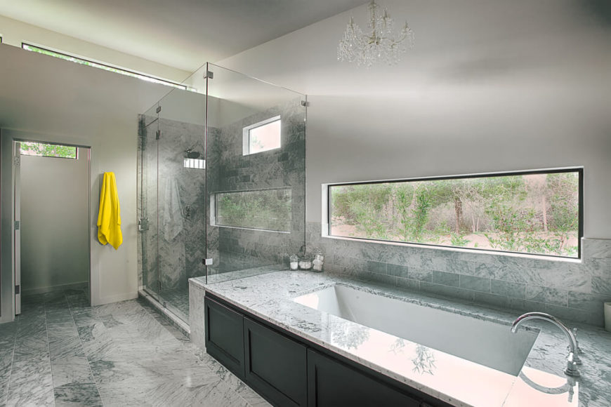 The bathroom contrasts the bright whites of the rest of the home with deep marble tones, throughout the flooring and bath areas. Large glass-enclosed shower stands next to the soaking tub, with natural light cascading in above.