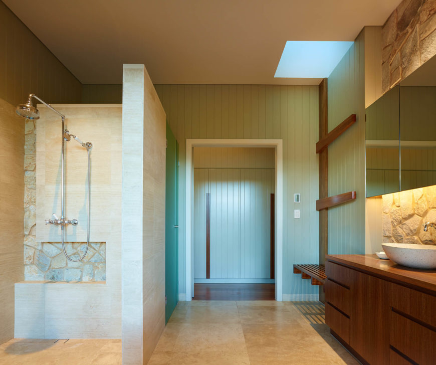 With a walk-in shower and sleek wood bench and drying racks, the bathroom is fully equipped with interesting, thematically cohesive details.