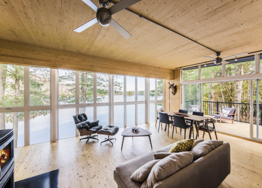 The sprawling open-plan space includes room for various living room furniture pieces and a lengthy natural wood dining table, standing near the full opened sliding glass patio doors.