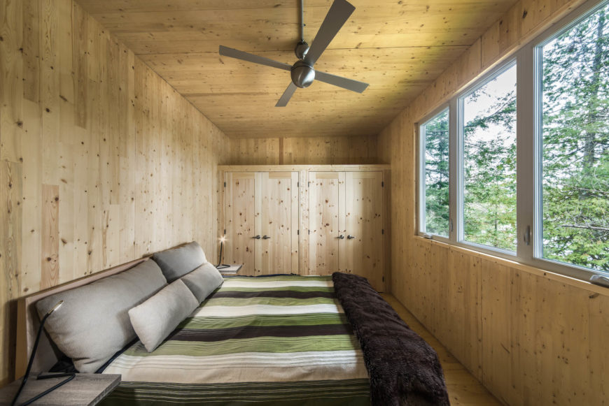 Master bedroom appears wrapped in natural wood panels from top to bottom, with built-in storage at the far end. The bed faces a set of large windows, facing the lake.