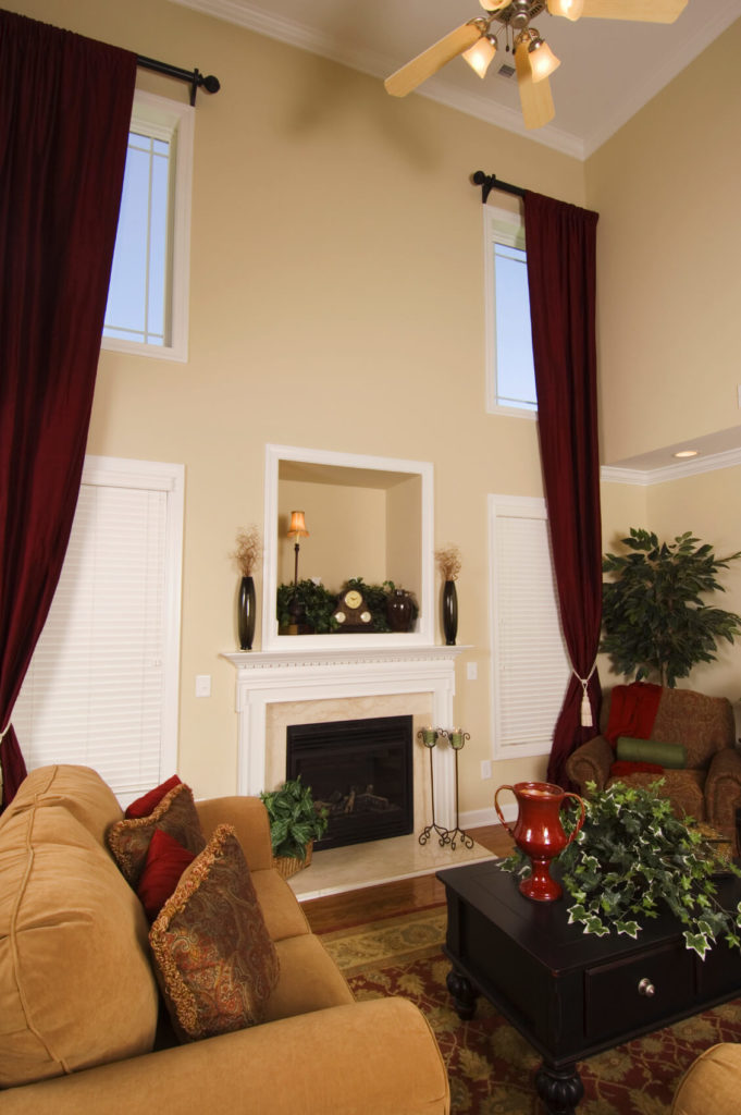 In a two-story great room, curtains can be used to frame an entire wall with layers of windows. The deep red of these ones are picked up by small accents throughout the space.