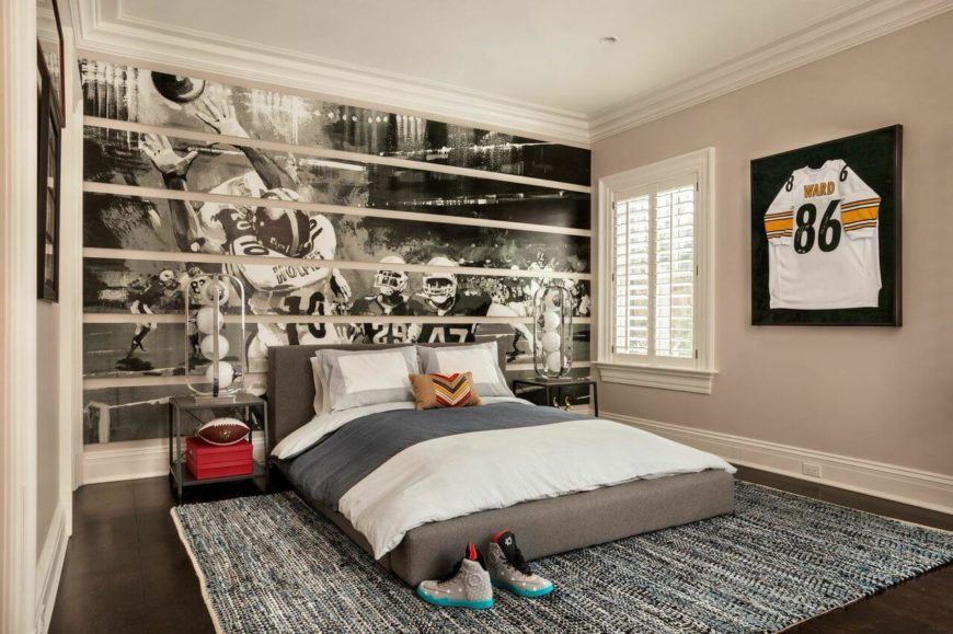 A masculine bedroom filled with sports memorabilia. The same dark hardwood floors as the rest of the home continue into this room, and the wall behind the bed has a fantastic black and white mural. The low-profile platform bed is upholstered in light gray.