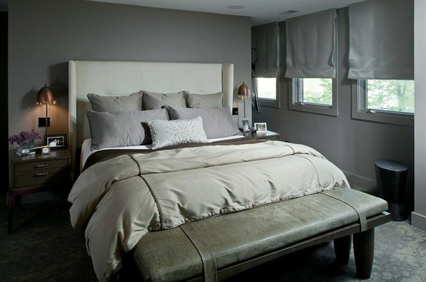The master bedroom is in a very contemporary gray with an upholstered wingback head board. The bench at the foot of the bed is in a subtle, light green alligator skin pattern.
