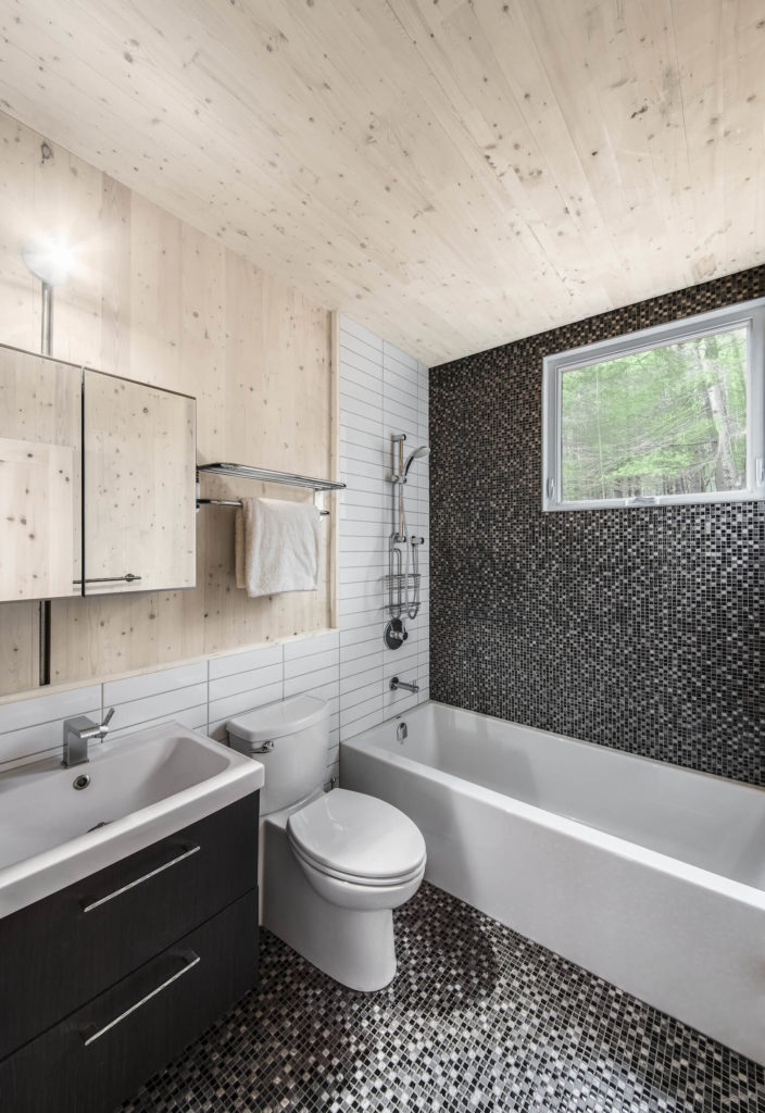 The bathroom marks a stylistic departure for the home, awash in greyscale micro tiles and white brick wall pattern.