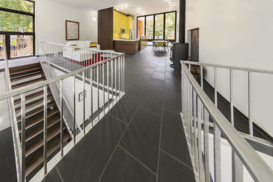 The large format tile flooring acts in fine contrast with the bright surroundings, seen here continuing through a catwalk suspended over the lower level.