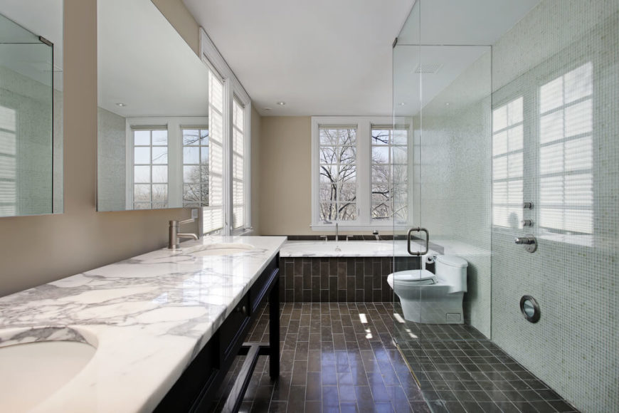 This sleekly modern bathroom sports a dark brick-styled tile flooring in brown, beneath both beige and micro-tile walls. A large glass-enclosed shower stands at right, across from a table-style dual vanity with marble countertop.