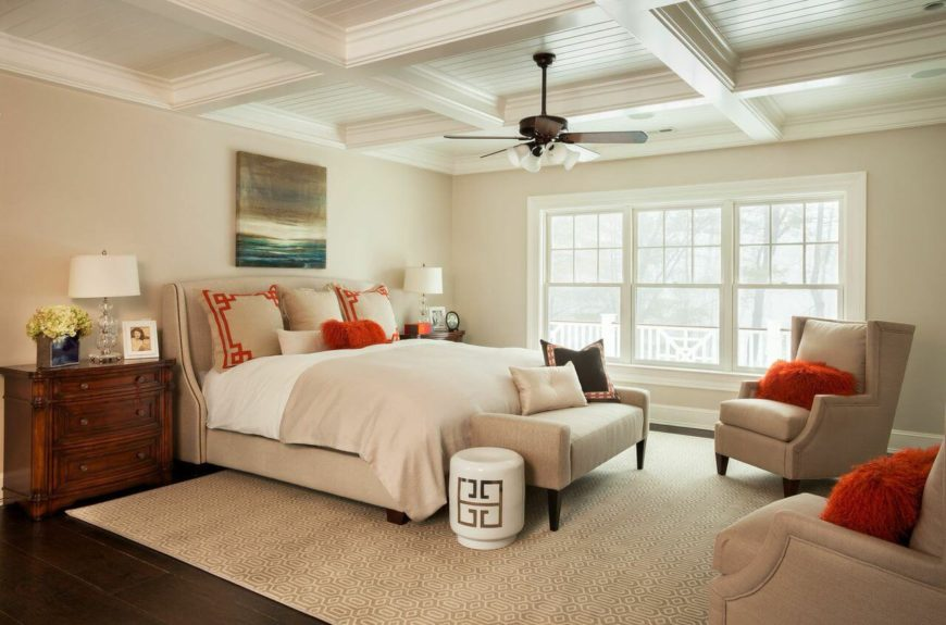 A contemporary bedroom with wingback chairs and a matching upholstered head board. Bright pops of red-orange in the fluffy throw pillows add the right touch of cheer to the mostly cream and dark hardwood bedroom. Beautiful coffered ceilings add elegance.