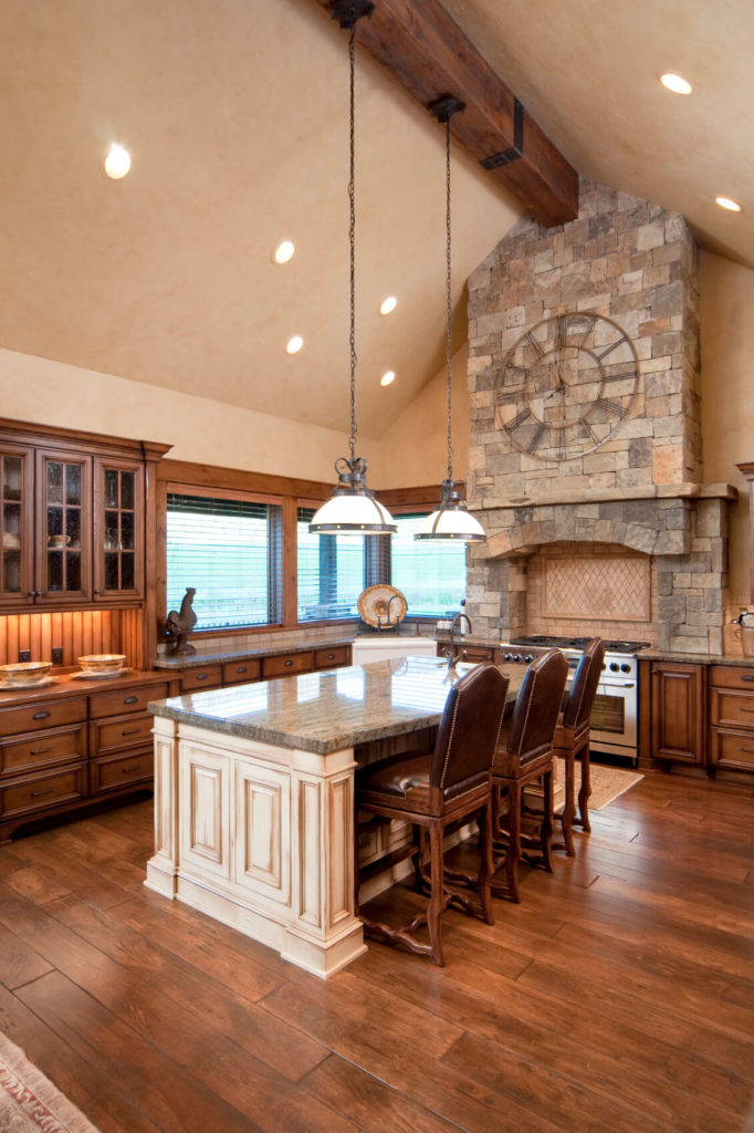 This magnificent home has a gorgeous brick vent hood with a stunning clock piece. The two-toned wooden floor and brushed wooden island really gives this space a country atmosphere.