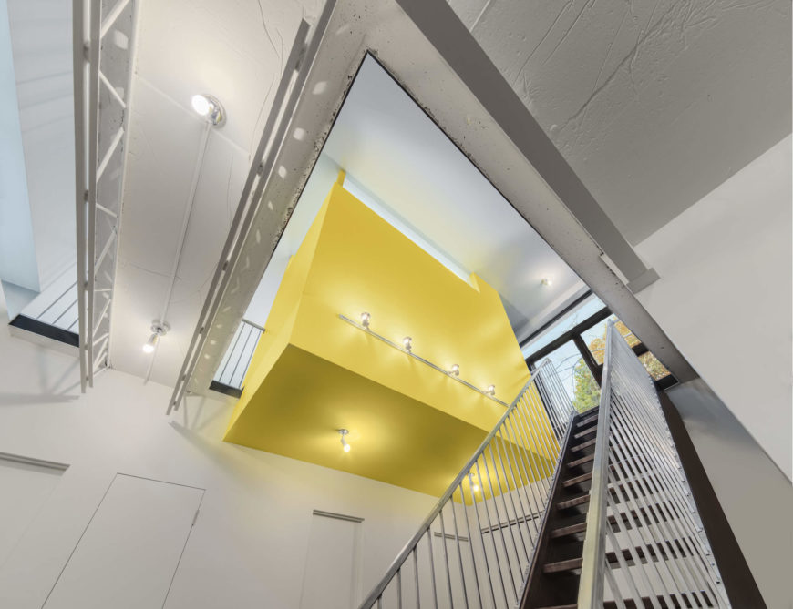 From below, the bathroom appears like a giant yellow block, suspended in open space within the home.