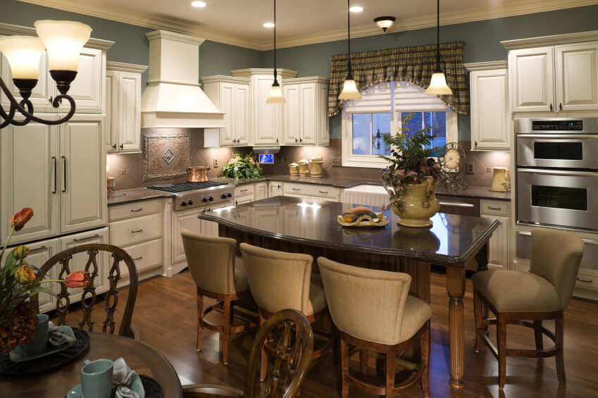 This large and detailed kitchen is flush with variety; textures and colors craft a wild interplay that makes for a detailed but not overly fussy appearance. The large island features black granite countertop, contrasting with both the hardwood flooring and white cabinetry.