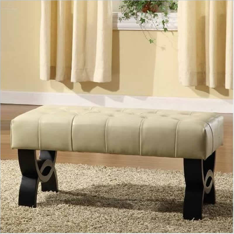 A long tufted ottoman in cream with dark wood legs that is perfect for two people to rest their feet on without taking up too much space in a smaller room.