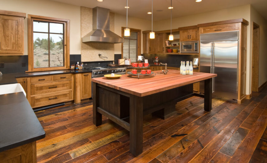 This rustic kitchen has a very country atmosphere. The worn look in the wooden floor and cabinets gives it personality and a handsome glow.
