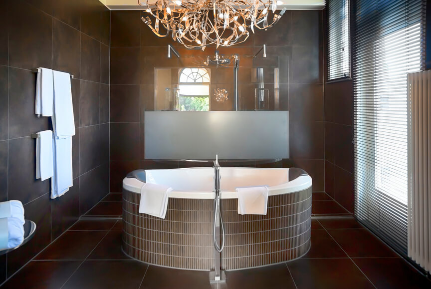 This square bathroom is wrapped in dark rust hued, large format tile from the flooring up, with a large soaking tub at center. Full height window at right adds natural daylight to the illumination provided by chandelier.