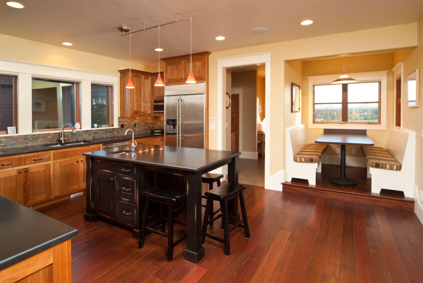 This lovely kitchen has deep red hues in the dark wood flooring. The colors stand out against the light paint on the walls and the dark counter tops.
