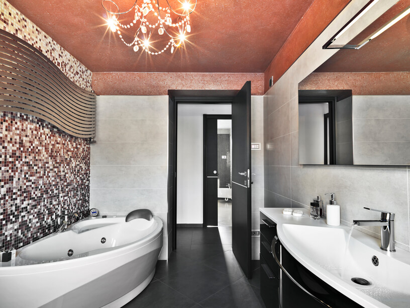 This modern luxury bathroom sports a uniquely carved jacuzzi tub and black and white vanity, over charcoal grey tile flooring. Grey marble walls are complemented by a micro-tile design over the tub.