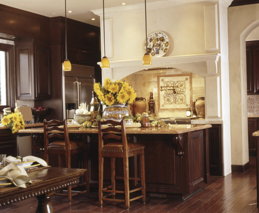 This elegant home has exquisite decor with splashes of yellow and gold. The dark hardwood flooring contrasts with the canary yellows in the lights and decorations.