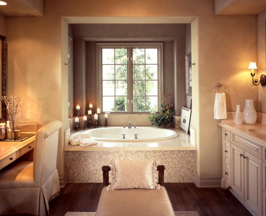 This cozy luxury bathroom, featuring a dark hardwood floor, centers on a large soaking tub beneath a window. Marble topped vanity at right sports intricate wood cabinetry, across from a small makeup desk at left, with lounge bench at center.