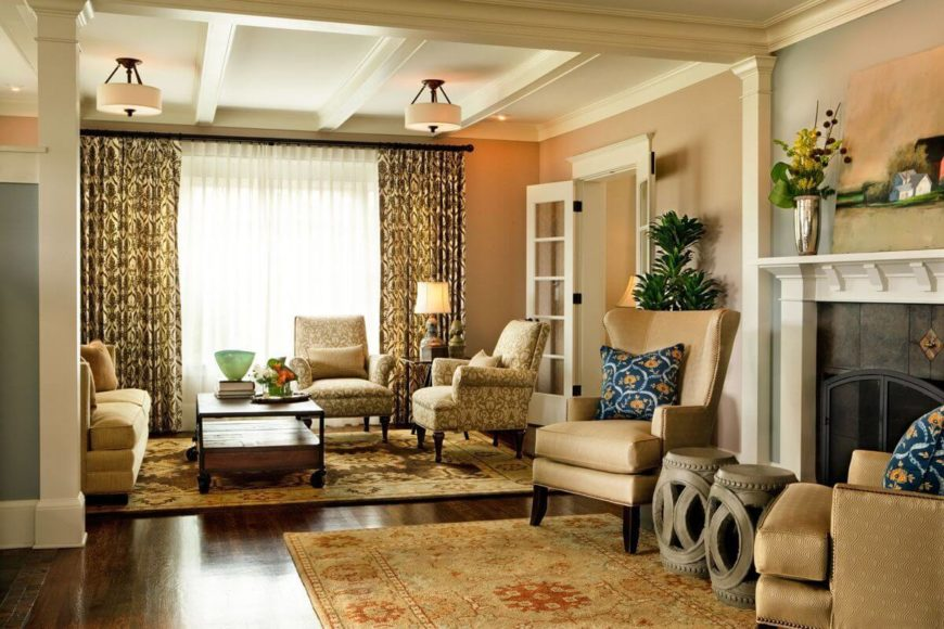 The formal living room space includes two separate seating areas: one near the spacious window and French doors to the foyer, and a small area near the screened fireplace. The dark hardwood flooring is covered by traditional rugs in beige, red, and brown.