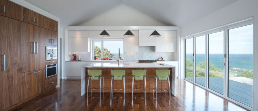 The home's kitchen is located on the second floor and is a mixture of glossy white cabinets and rich wood with a beautiful grain. Pale green modern barstools sit at the eat-in kitchen island. A set of sliding glass doors lead out onto the patio, with a view of the Iverness harbor.