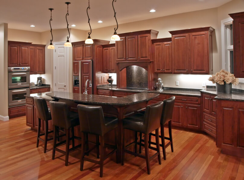 The creamy texture of this amber hardwood flooring is just light enough to contrast with the deeper colors in the cabinets. The hues get even darker in the island and bar chairs.