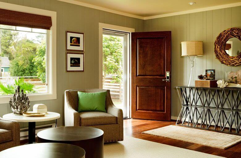 The cheery entrance way is characteristic of a ranch, opening into the living room. The beautiful tone of the dark bamboo flooring pulls color out of each piece of furniture in the room. A large, seamless window to the left of the door lets in ample natural light.