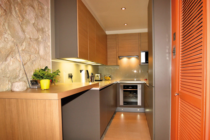 The lengthy, narrow space manages to fit in every modern convenience, including a small dining surface at left. The variety of textures and tones creates a wide visual palette.