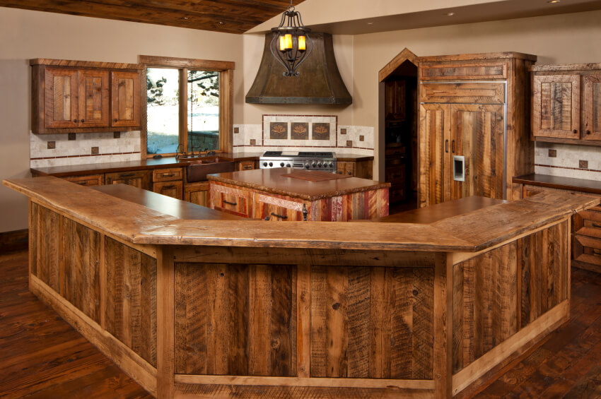 This unique country kitchen is made up almost entirely of wood. Dark hardwood flooring, as well as natural wood on the face of the countertops and cabinets.