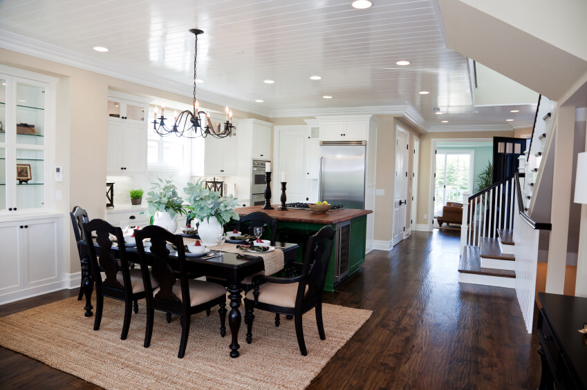 This truly open-plan kitchen and dining room combination stands at the center of this home, connected to the main foyer and staircase at right. A unique green painted island sits at center, topped with rich hardwood.